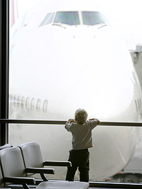 boy in airport looking at airplane