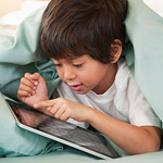 boy playing with digital tablet in bed