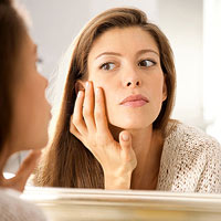 woman checking out her skin in mirror
