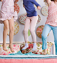 three girls jumping on a bed