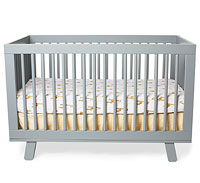 Grey crib with white giraffe sheet and skirt