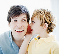 boy whispering in father?s ear