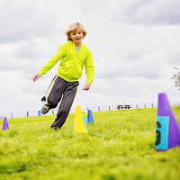boy running through cones