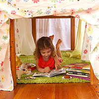 child reading under table