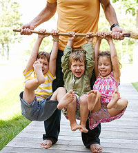 Three kids hanging on dad