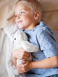 Boy laying down with stuffed animal