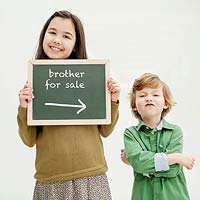 Girl holding ?brother for sale? sign