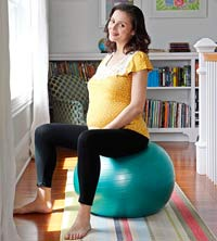 pregnant woman sitting on exercise ball