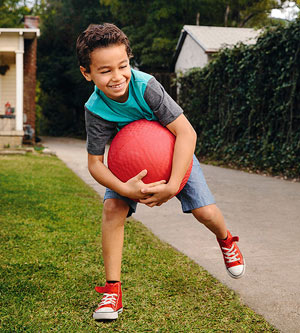 Boy with red ball in driveway