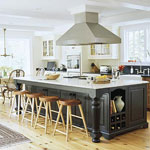 Large kitchen with an oversize island with a built-in range and a stainless-steel hood