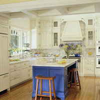 Traditional kitchen with white cabinets, a blue island, and a coffered ceiling