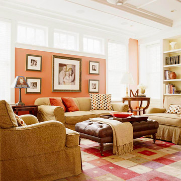 a colorful living room with salmon-color walls and a bold rug