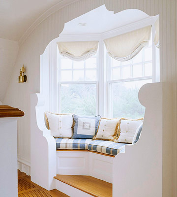 window seat set into a bay on this upper level landing serves as one