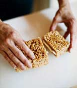 Rice Crispy Treat pieces being put together by the frosting