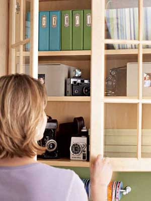 cabinets with glass front doors that store photoboxes and vintage cameras