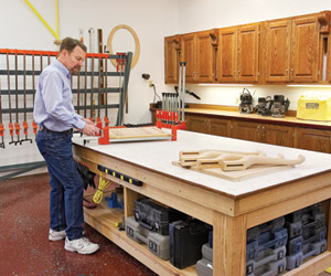 Man at workbench with red clamped object