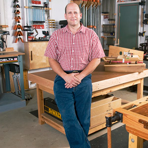 Man standing by workbench with red checker shirt on