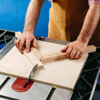 Board on tablesaw with hands holding a type of v shape jig