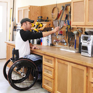 Man in wheel chair putting object on wall