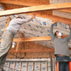 2 men putting insulation in ceiling