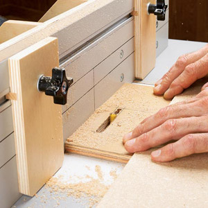 2 hands on board pushing it thru router jig