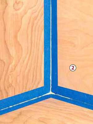 Corner of wall with blue tape and glue coming thru tape