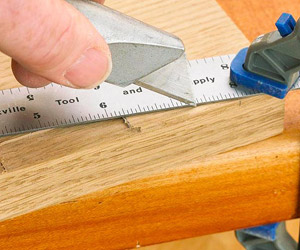 Hand using utility knife with metal ruler
