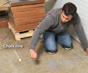 Man on knees making chalk line
