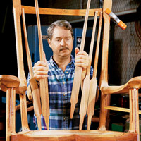 Man putting slats on back of rocking chair