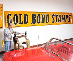 Sign on wall ?Gold bond stamps, man by red car