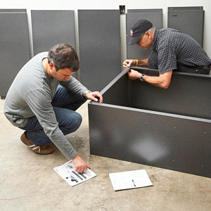 2 men working on corner of cabinet