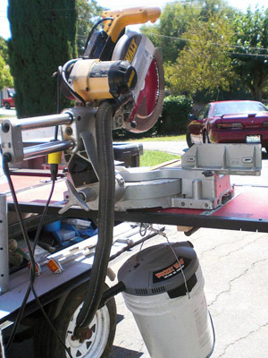 Closeup of mitersaw with shop vac attached