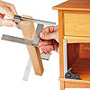 Hands holding jig by cabinet