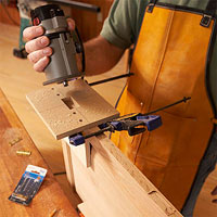Holding gray router above jig and board