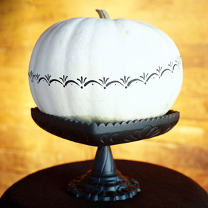 white and black painted pumpkin on stand