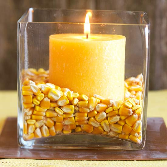 Yellow candle surrounded by corn in a square class holder