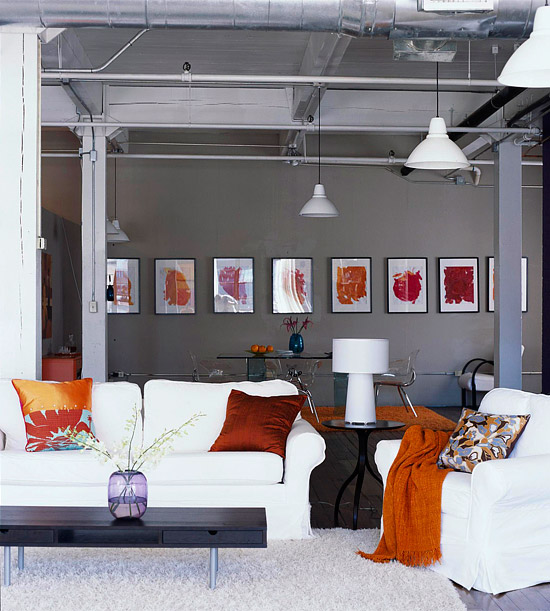 Gray Loft Living Room With Exposed Duct Work And Orange Accents
