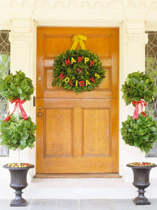 To decorate your front door with a classic look, craft a Christmas wreath from live materials, such as long pine needles, boxwood, or pinecones.