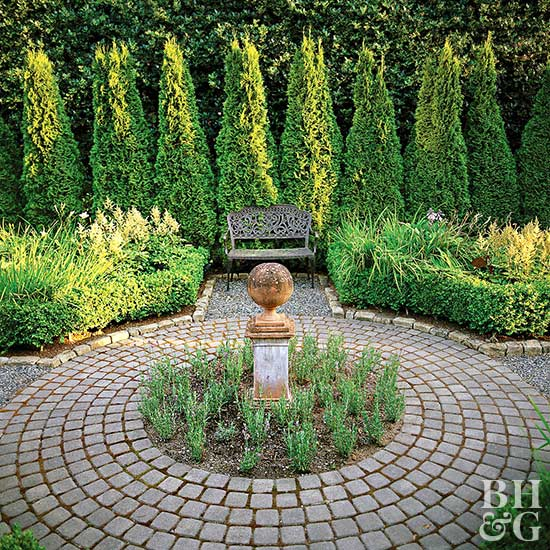 round brick patio with shrubs and hedges