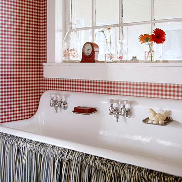 Home decor inspiration with an Americana twist. Country farm sink skirted with blue and white stripes against red and white gingham wallpaper. #countrystyle #farmsink #farmhouse #redwhiteblue #americana #cottagestyle