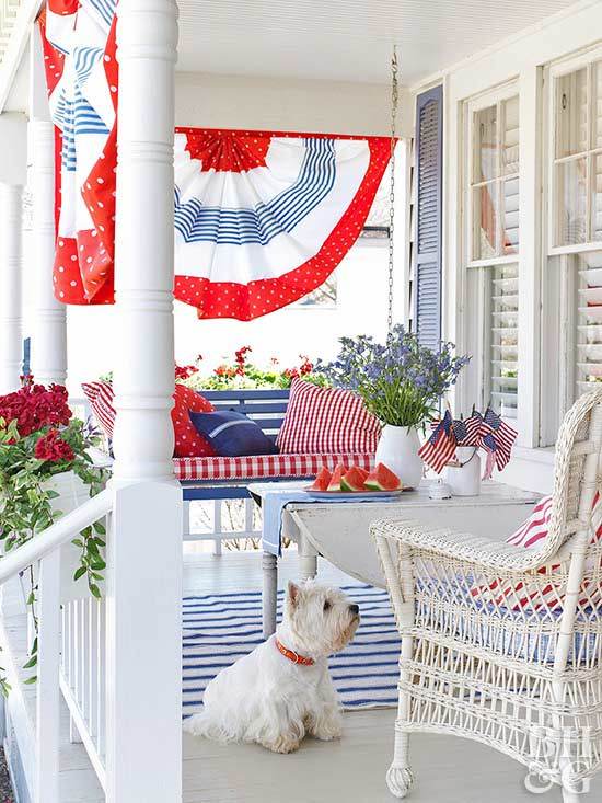July 4th porch with traditional decor and southern charm. Red, white, and blue decorate this white porch with white scottie dog, blue porch swing with red gingham cushion, and white wicker chair. #patriotic #porch #southern #redwhiteblue #4thofjuly #july4th #memorialday #americana #cottagestyle