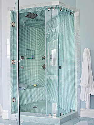 An entry door straddles a clipped corner to make the neoangle shower a  popular choice for small bathrooms because it offers accessibility in tight  spaces.
