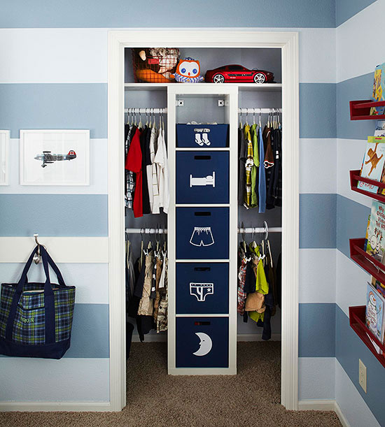 a customized small walk in closet layout amplifies usable space this center tower acts as a dresser of sorts it holds pullout bins sporting drawn figures - Small Walk In Closet Design Ideas