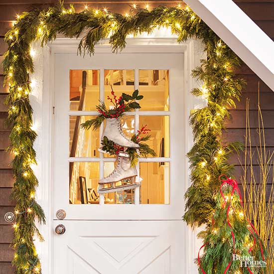 trio of wreaths flanked by two planters with string lights to create outdoor lighted Christmas decorations.
