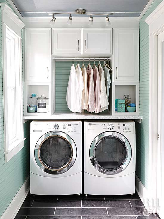 washer dryer with built in cabinets above and hanging clothes rack