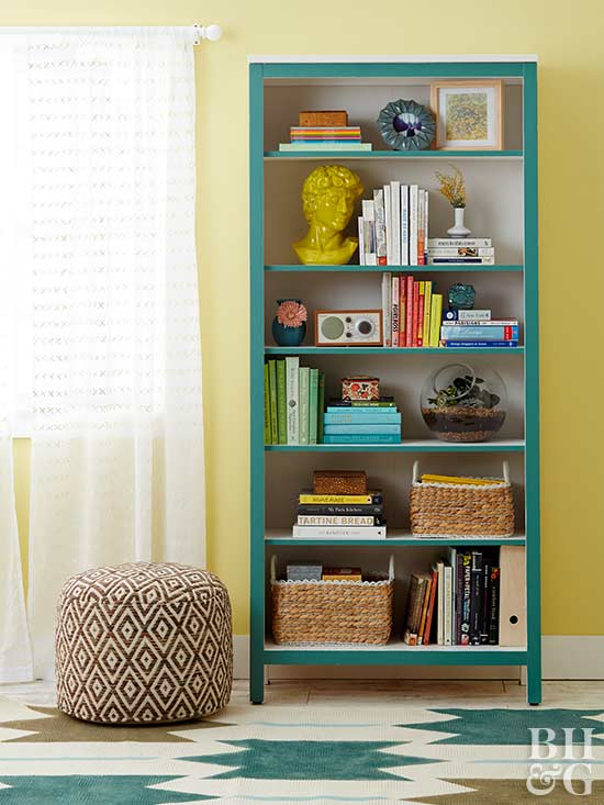book shelf, shelf, pouf, yellow wall, painted rug