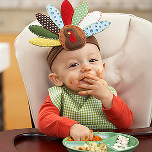baby in high chair with turkey headband
